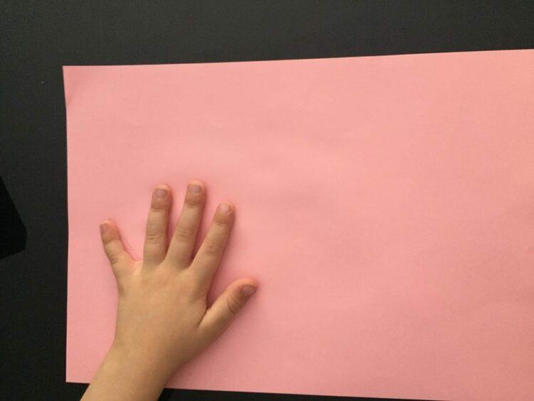 Main sur feuille cartonnée rose